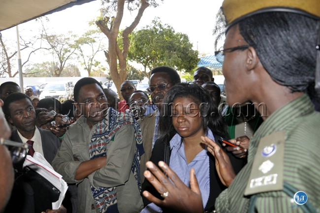 Zambia police spokesperson Charity Chanda talks to UPND officials who had refused to take their leader to the second floor of the police headquarters.