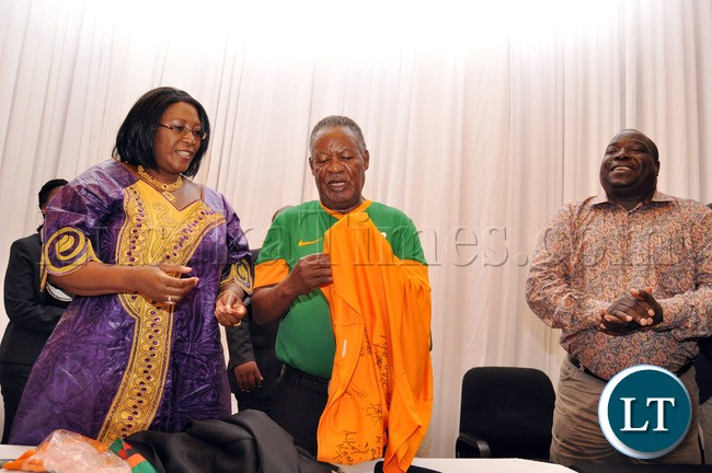 President Sata  trying  to wear the Chipolopolo Jersey by First Lady Dr Christine Kaseba as Sports minister Chishimba Kambwili looks on