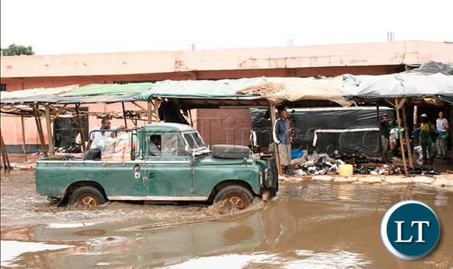 A LandRover finding its way through the flooded Njashishi Road in Kanyama Compound in Lusaka
