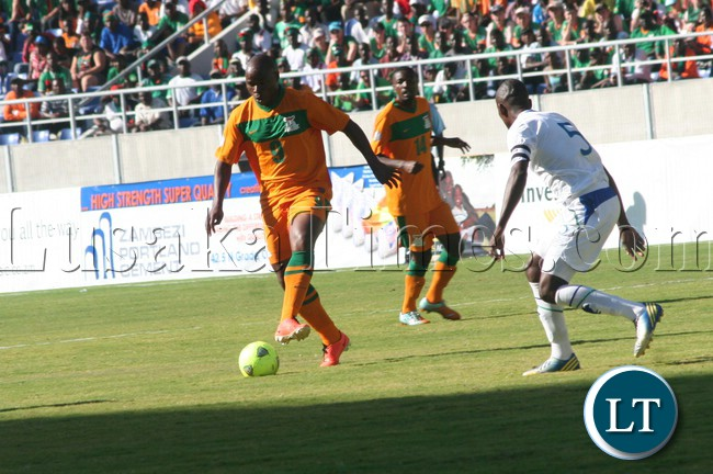 Collins Mbesuma (l) is challenged for the ball by Lesotho captain Moitheri Ntobo on June 8 in 2014 World Cup qualifier while Zambia midfielder Noah Chivuta (background) looks on. Zambia beat Lesotho 4-0.