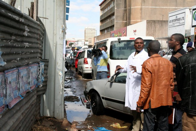 Local Government Deputy Minister John Kufuna (l) talks to Lusaka City Council Senior Environmental Health Officer Edgar Mulwanda (r) about the dirty posters and  stagnant water on Chachacha Road in Lusaka during his Inspection Tour for Performance Based Contractor Projects,