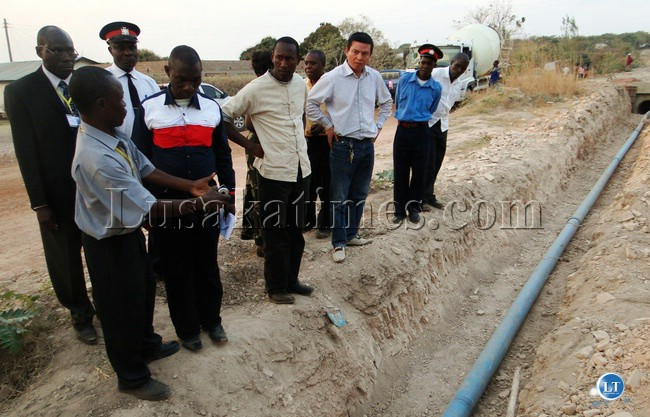 CHAMBESHI Water and Sewerage Company Mpulungu District Manager Charles Phiri second (left) explains how his company has been failing to supply adequate water to Mpulungu Township residents due to the breaking down of water pipes by a road construction China Geo South Africa company.