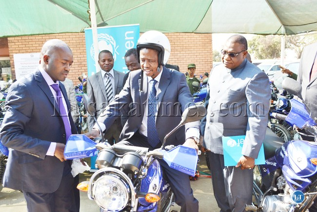 Home Affairs Minister, Edgar Lungu tries out one of the 70 motorbikes donated by UNICEF to the Department of National Registration, Passport and Citizenship in Lusaka yesterday. Looking on is UNICEF representative Iyorlumun Uhaa