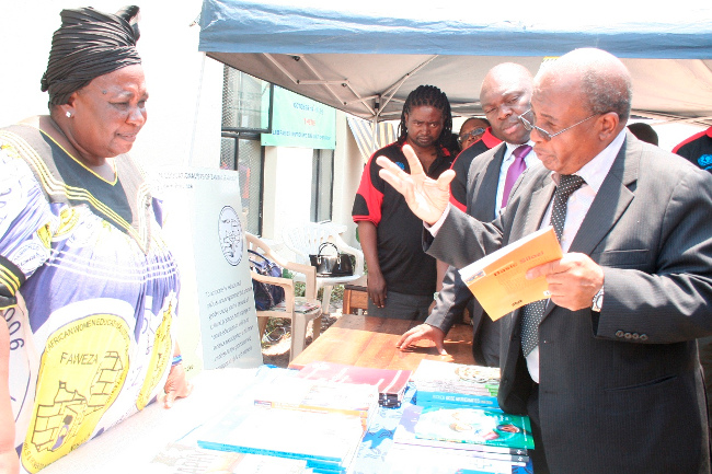 FAWEZA Mongu District Charperson Limpona Nakwebwa (l) listens to Education Minister Dr. John Phiri (r) the books as Western Province Ps Amos Malupenga looks on during the Launch of the National Libraries Week at Mongu Librabry in Mongu Western Province