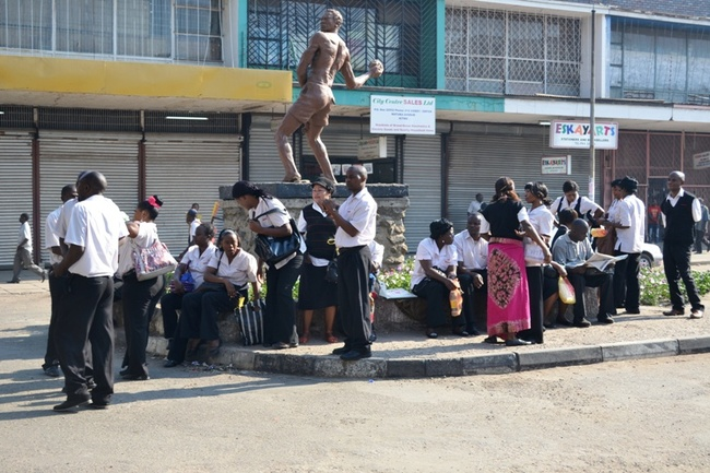 Striking workers from Shoprite Kitwe branch  seated at the freedom statue  a few meters away from the  Shoprite premises