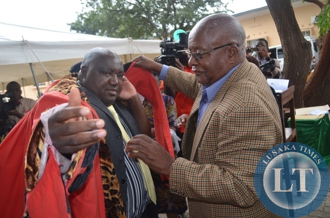 Southern Province Minister Daniel Munkombwe (right) dresses the newly elected mayor for Livingstone Milford Maambo (left) during the installation of the mayor and deputy mayor in the tourist capital