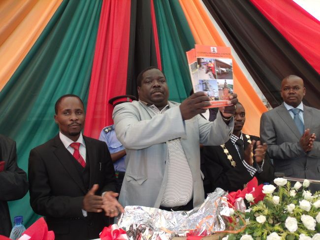 MINISTER of Youth and  Sport Chishimba Kambwili displays a copy of the 2014-2018 Luanshya District Strategic Plan, as District Commissioner Harold Mbaulu(left) and Luanshya Mayor Nathan Chanda Bwalya (right) and Town Clerk Alex Mwansa looks on during the launch of Strategic Plan at Luanshya Civic Centre grounds