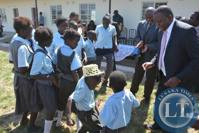 Deputy Minister in the office of the vice President Davis Mwango and Chibombo District Commissioner Felix Mangwato joining Namayani pupils in celebrating the handover of the classroom and the house during the handover of the 4 school built in Chibombo District at Namayani Primary School