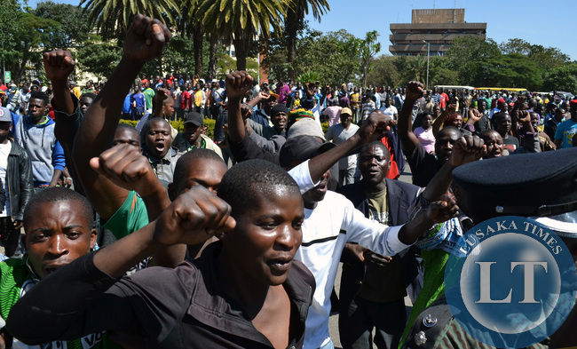 Patriotic Front cadres chant slogans outside the Lusaka High Court grounds as President Michael Sata attended a court case there in Lusaka