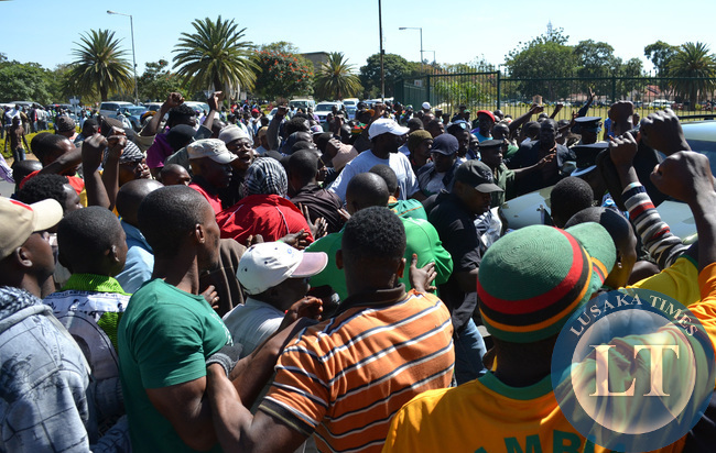 Patriotic Front cadres try to catch a glimpse of President Michael Sata at the High Court in Lusaka