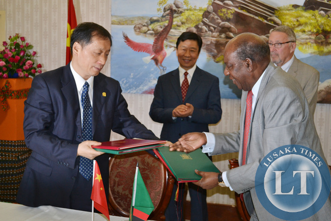 Finance Minister Alexander Chikwanda exchanges folders with Chinese Vice Minister of Commerce Li Jinzao (left) after signing various agreements in the presence of Vice President Guy Scott and Chinese Vice President Li Yuanchao (second from left) look on at Government House in Lusaka