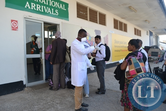 A HEALTH official going through a medical card of a passenger who had just disembarked an international flight at the Simon Mwansa Kapwepwe International Airport in Ndola . The process is part of screening for Ebola at entry points into Zambia.