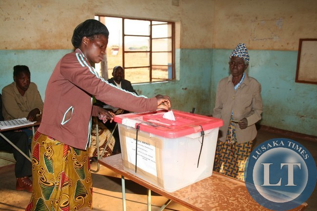 JOYCE Daka, casts a vote on behalf of her visually impaired grandmother, Tiwamyenji Miti ( right) cast her vote at Mtaya Basic school polling station in a Kasenengwa parliamentary by-election in Chipata