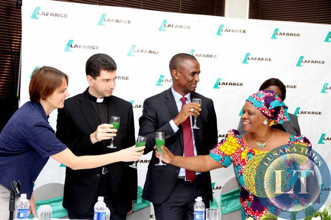 First Lady Esther Lungu toasts with Lafarge  Zambia Chief Executive officer's wife Isabel Rigaux (l) as Deputy of the Catholic Apostolic Nunicature Fr Marco and Deputy minister of Justice Keith Mukata  looks on during the Launch of the Lafarge Foundation at Twangale Park in Chilanga, Lusaka on February 19,2015 -Picture by THOMAS NSAMA
