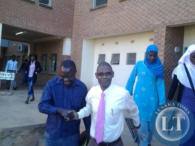 Chilufya Tayali is congratulated by YALI Governance Adviser Isaac Mwanza after he was acquited
