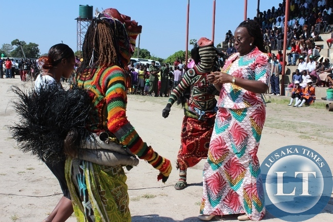 Community Development Minister Emerine Kabanshi (r) joins the makishi dancers during Labour Day Celebrations at Mongu Stadium in Mongu on Friday.