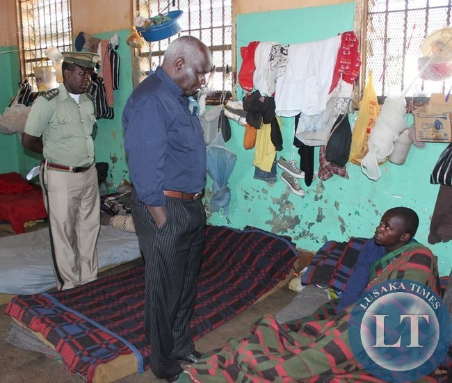 Home Affairs Deputy Minister Panji Kaunda (middle) greets an inmate at Livingstone Central Prison