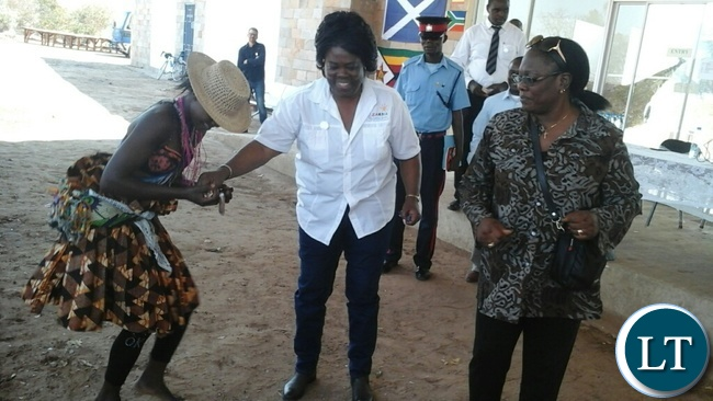 Tourism and Arts Minister Jean Kapata (middle) joins a cultural dancer as former deputy minister in the MMD Government Grace Njapau (right) looks on during the Insaka International Arts Exhibition at the Livingstone Art Gallery.