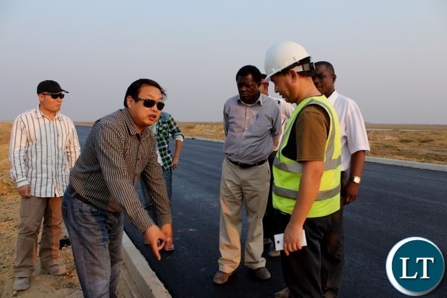 AVIC International Zambia Limited Site Manager Chen Yiju (l) explains as his colleague Chief Engineer Xie Zhanqi (r) and Mongu District Commissioner Susiku Kamona (c) listen during a tour to inspect work progress on the Mongu-Kalabo Road Project