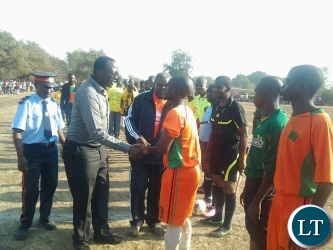 Eastern Province Permanent Secretary Chanda Kasolo flanked by Malambo Member of Parliament Jacob Shuma greeting Dushambe FC skipper before the kick off between Dushambe and Mambwe Warriors in Mfuwe on Sunday.This was during the Kavulamungu Bargain Centre sports tournament.Pictures By JULIUS PHIRI