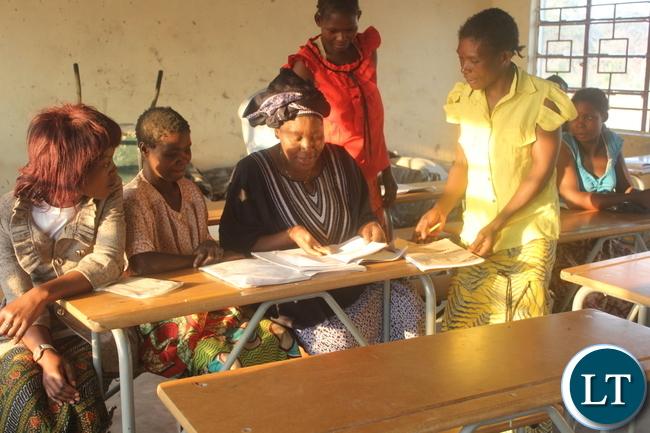 Ms. Nawakwi checks some books of grade 4 adult pupils at Milulu Primary School.