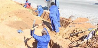 Construction Workers digging a drainage for one of the Serenje district township roads being upgraded to bituminous standards.
