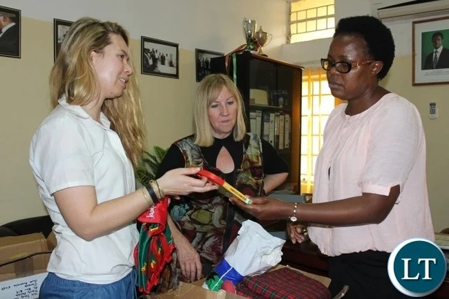 Lewanika General Hospital Medical Superintendent Dr. Mutanga Mapani (r) receives some children's toys for the Children ward from Australian Music Teacher Cate Dyer (l) as Dignity Zambia CEO Sandy Clark (c) looks on during the donation the hospital in Mongu