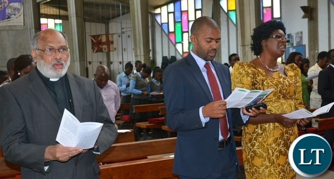 Minister of youth and sport Vincent Mwale(c) sings along with Rev Charlie Thomas(l) and council chairperson of the scripture union of Zambia Margaret Siwale during the scripture union of Zambia thanks giving service at the cathedral of holy cross in Lusaka