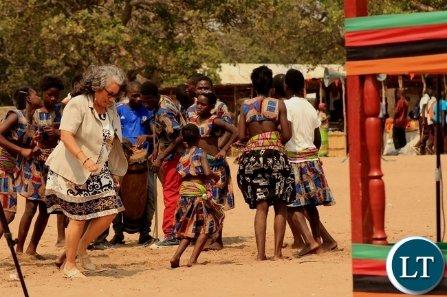 USAID Zambia Education Office Chief Iris Young joins school children in dancing during the celebration of International Literacy Day at Mulambwa Primary School in Mongu