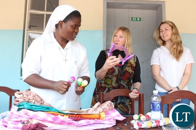 Dignity Zambia CEO Sandy Clark (c) talks to Holy Cross Girls Secondary School Manager Bibian Mbao (l) as Australian Music Teacher Cate Dyer (r) looks on during the donation of assorted items to the school in Mongu