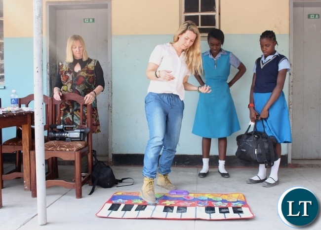Australian Music Teacher Cate Dyer (c) shows Holy Cross Girls Secondary School pupils how to play a floor piano as Dignity Zambia CEO Sandy Clark (l) observes during the donation of assorted items to the school in Mongu