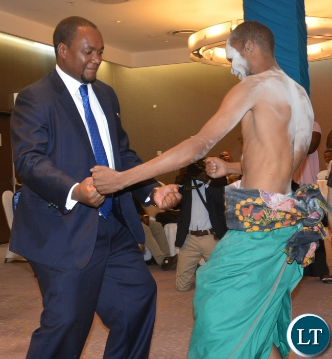 Deputy Minister of Commerce and Trade Miles Sampa(l) joins a dancer from twatasha cultural group during the Zambia Bureau of Standards launch of the new logo at hotel intercontinental