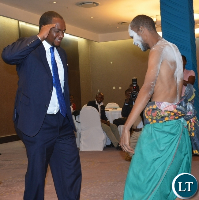 Deputy Minister of Commerce and Trade Miles Sampa(l) salutes for a dancer from twatasha cultural group during the Zambia Bureau of Standards launch of the new logo at hotel intercontinental