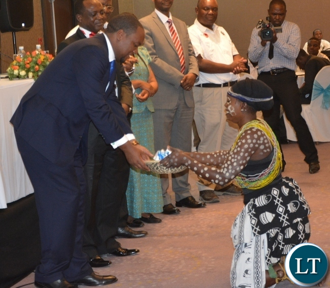 Deputy Minister of Commerce and Trade Miles Sampa(l) being given the keys from one of the dancer of twatasha cultural group during the Zambia Bureau of Standards launch of the new logo at hotel intercontinental