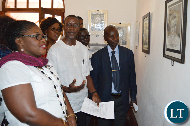 Mazabuka based artist Alec Lishandu (middle) shows Choma district administrative officer Vincent Sikanyela (in a jacket) and Choma Museum director Bevine Sangulube (left) some of his artistic works during opening of an art exhibition at the museum
