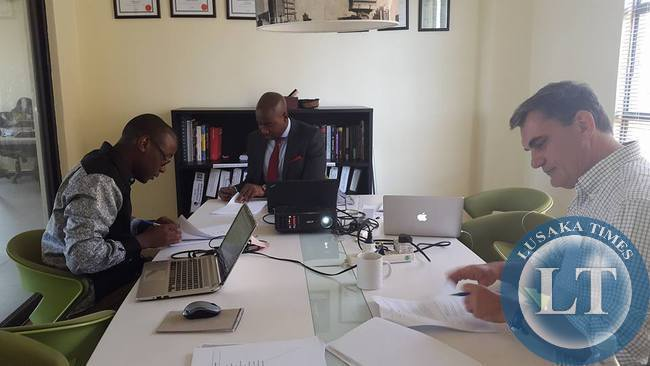 Dot Com Zambia CEO , Mawano Kambeu (l) with Jito Kayumba (c) Managing Partner at Kukula Capital and Vincent Kouwenhoven (r) Managing Director of eVentures Africa Fund signing the investment agreement