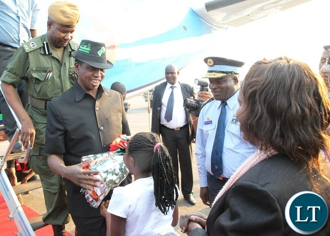 PRESIDENT Edgar Lungu receives a bouquet of flowers from a 10 year old girl at Solwezi Airport