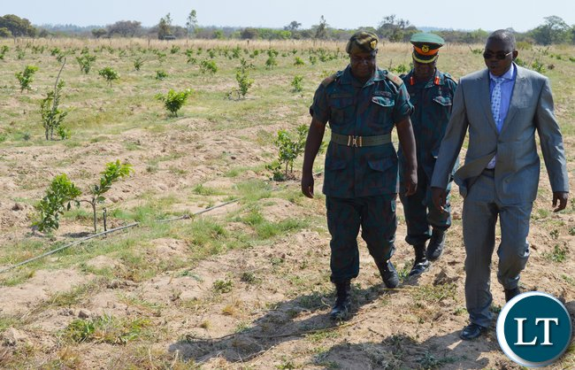 Defence deputy Minister Christopher Mulenga (in a suit) with Zambia National Service unit Choma commanding officer Lieutenant-Colonel Jimmy Kafumukache (far left) on tour of ZNS orchard in Choma