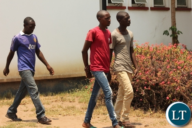 Hatch Bril (c) arrives at Mongu Magistrate Court for trial facing sodomy charges yesterday. Hatch is 27 years old, a hair dresser in Mongu and all along has been portraying as a woman hence deceiving men to fall for him.