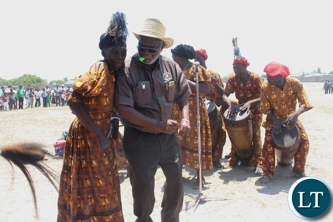 Labour Minister Fackson Shamenda (l) joins the Mbwanjikane Cultural Group in dancing during the 51st Independence Anniversary celebrations at Mongu Sports Stadium