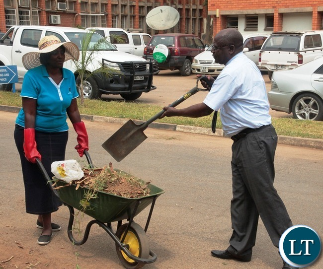 Ministry of Information and Broadcasting Service Permanent Secretary Godfrey Malama load the west in the wheelbarrow whilst his Human Resource Director Christine Mushanga is holding the wheelbarrow during the relaunch of KEEP ZAMBIA CLEAN at Mass media