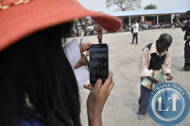 A 'tourist' uses her mobile phone device to record images of a resident who was is dancing during the Mukulapembe Traditional Ceremony in Luwingu recently