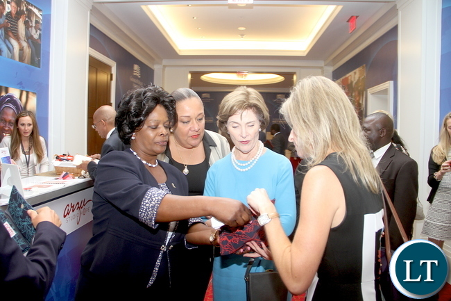 First Lady Esther Lungu (L), Former USA First Lady Laura Bush,  Haiti First Lady Sophia Martelly   (second from (L) and Charity Wallance  (R) admires a wallet (pace) when they visited a market place during the Global Women's Network Summit at George W. Bush Presidential centre in Dallas, Texas on Tuesday, September 22,2015 -Picture by THOMAS NSAMA