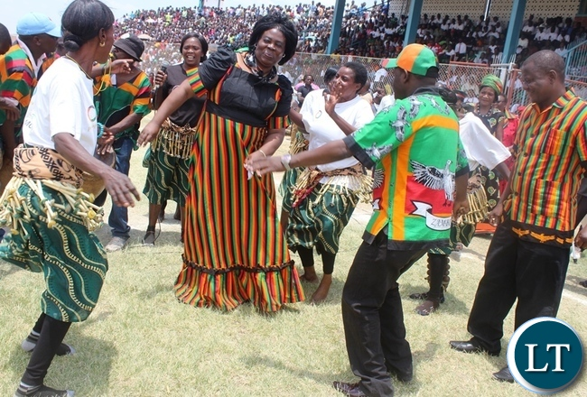 Tourism and Arts Minister Jean Kapata (centre) with Transport and communications deputy Minister James Kapyanga join the Chibwelamushi cultural dance during this year's fifty-fith Independence day celebrations at Godfrey Chitalu Stadium in Kabwe today.Looking on (far right) is Central Province Minister Davies Chisopa