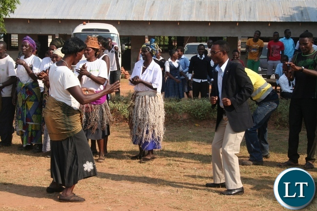 Mutanda secondary school deputy headteacher Isaac Lijimu (r ) joins the Mukumbi Ibaloli culture group in dancing the hunters dance locally known as Katembo during the official handover of a modern 1 x 3 science laboratory constructed by Lumwana mining firm at total cost of K1million