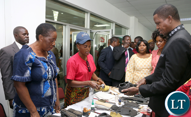 President Edgar Lungu talks to Gladys Mpungu and Matildah Kasonde of Rainbow Sovew shoes of Luansya during the exhibition at Mulungushi confrence Centre for the National Women Economic Empowerment Expo, which was Promoting Young Women enterpreneurs as a Change agents for National development . Picture By Eddie Mwanaleza/ Statehouse. 13-10-2015.