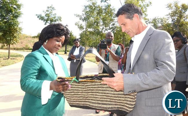 Healthier Lives World Wide  President  and Chief Executive officer Bruce Wilkinson  presents a hand bag he bought from Chikumbuso Women Club of Zambia to First Lady Esther Lungu during the Global Women's  Network  Summit at George W. Bush Presidential Centre in Dallas, Texas on Monday, September 21,2015 -Picture by THOMAS NSAMA