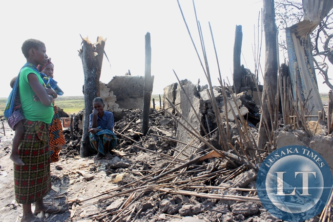 A family mourns as they look at the remains of their burnt house in Imuba Village of Katongo Lower area in Mongu after the whole village was burnt to ashes.