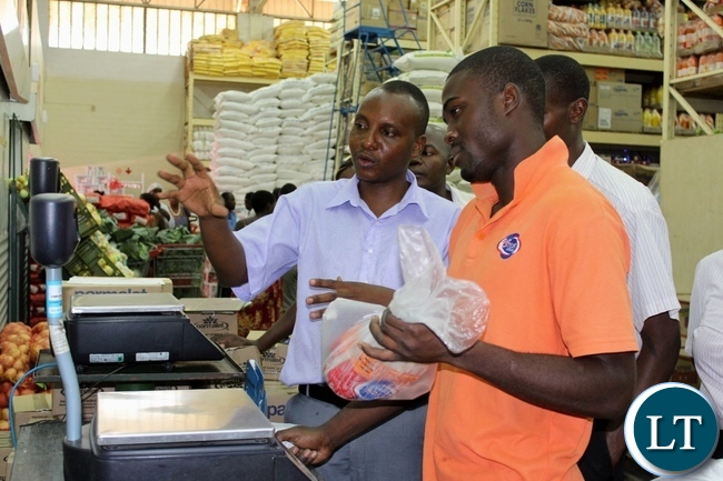 Western Provincial Competition and Consumer Protection Commission (CCPC) Investigator Mutemwa Nakambowa (l) explaining to a Shoprite worker during an Inspection and Sensitization Tour to Traders to observe the CCPC Act in Mongu