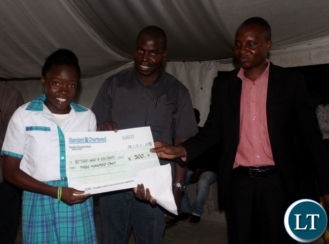 Best debater Muleya Luyando (l) of Holy Cross Secondary School displays her cheque with Mongu District Education Board Secretary Mulonda Sendoi (c) and Western Provincial Competition and Consumer Protection Commission Investigator Mutemwa Nakambowa (r) during the Competition and Consumer Protection Commission School Clubs debate in Mongu